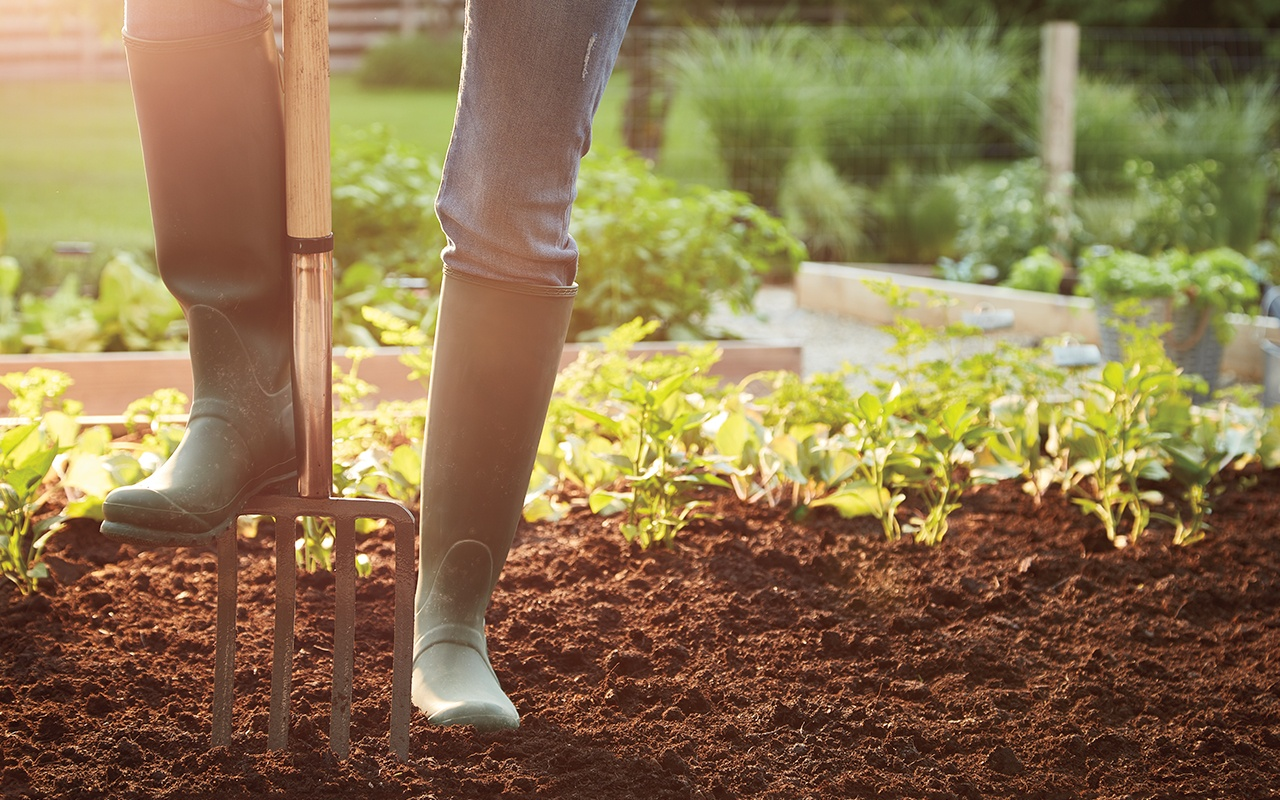 woman-gardening-boots-on-pitchfork-in-dirt